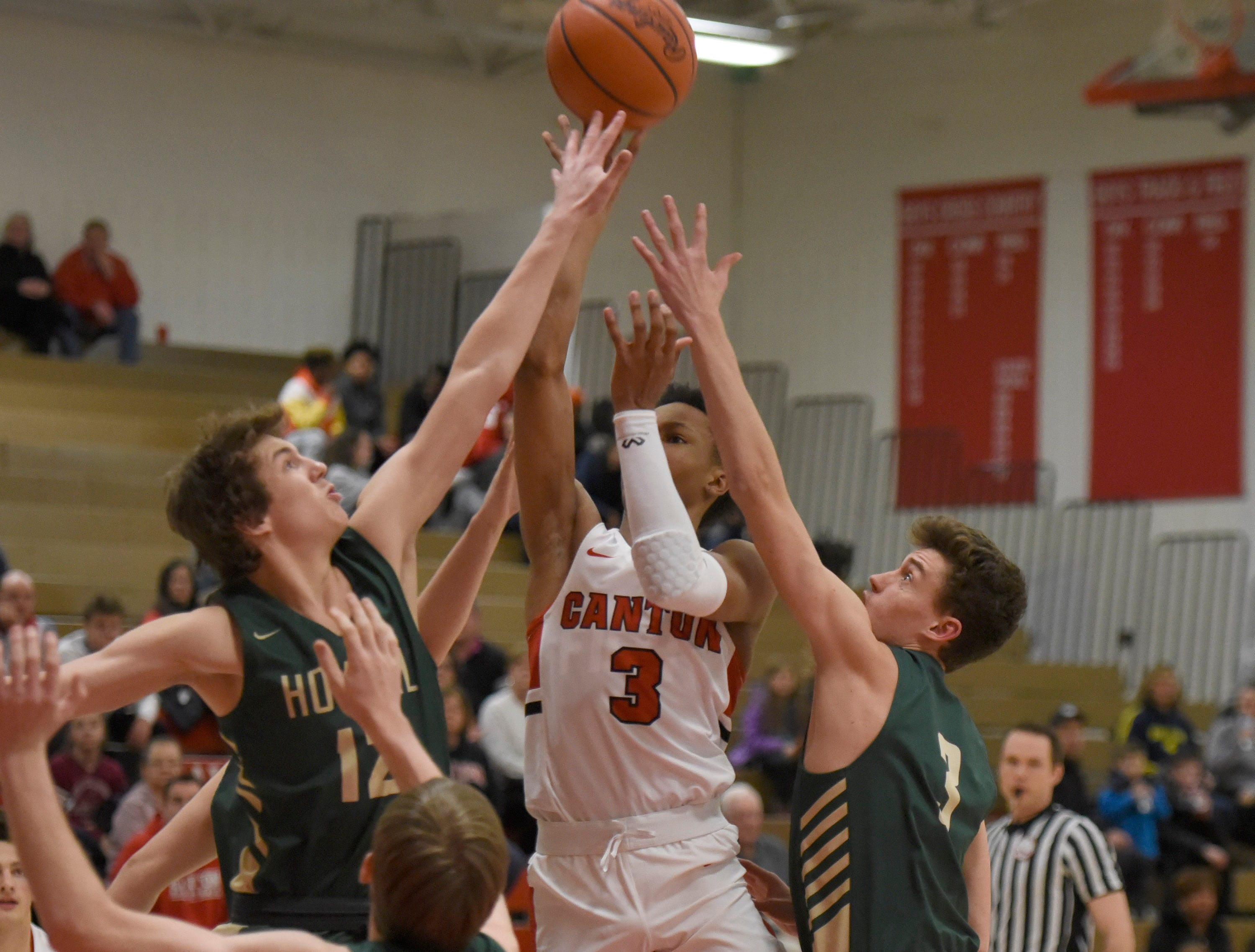Canton B. Artis White (3) drives against Howell players Tony Honkala (12) and Kip French (3) KLAA match up played at Canton Jan. 15, 2019
