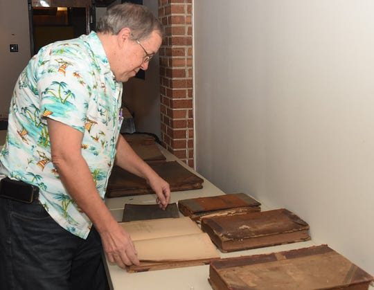Neal Bertrand browses through vintage ledgers at the monthly meeting of the Imperial St. Landry Genealogical Society.
