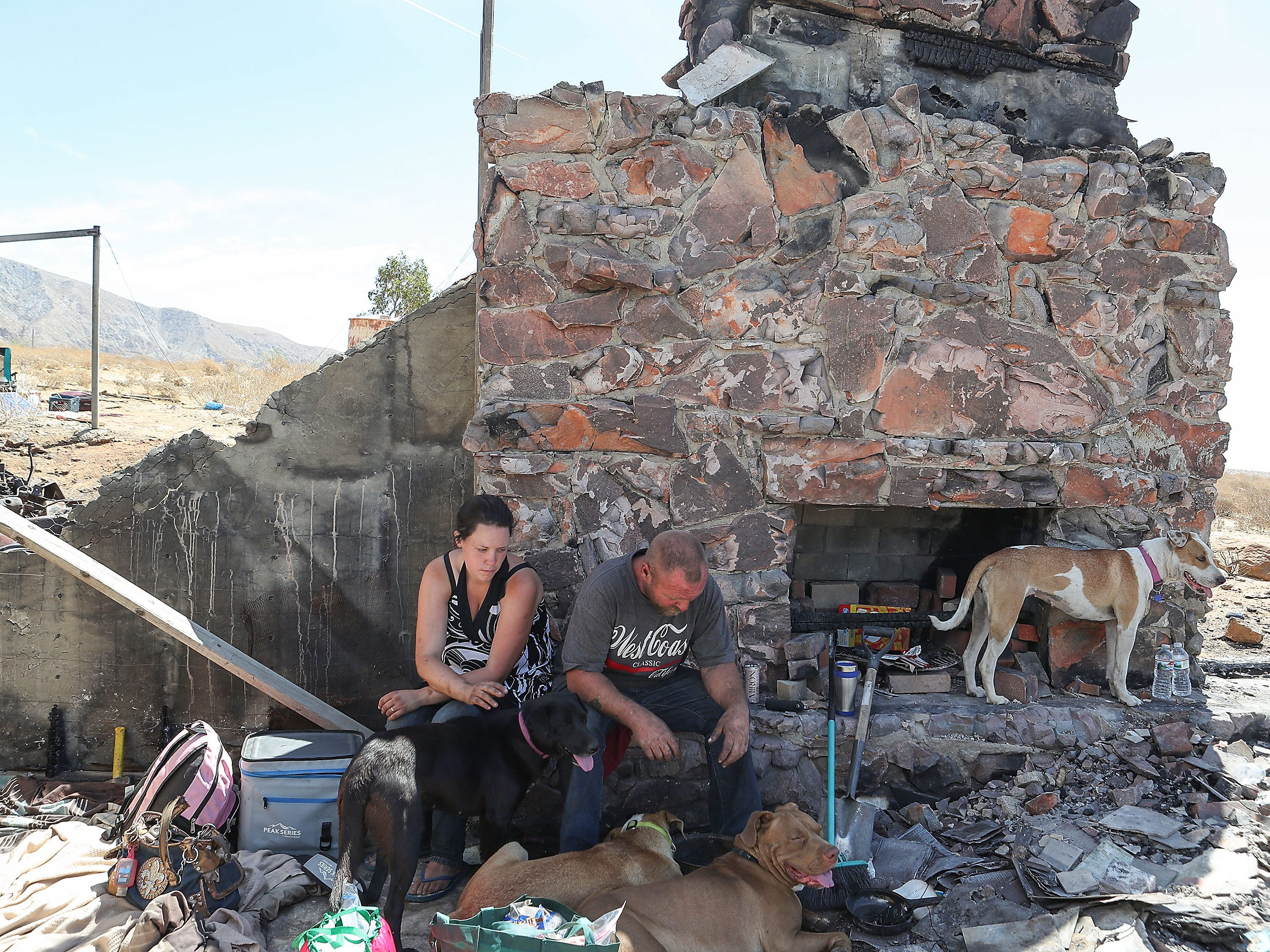 Bryan Hensley and Carene Riale endure triple-digit temperatures in the shade of a burned-down house in Whitewater.  The two were displaced from the Coachella encampment in May of 2018.