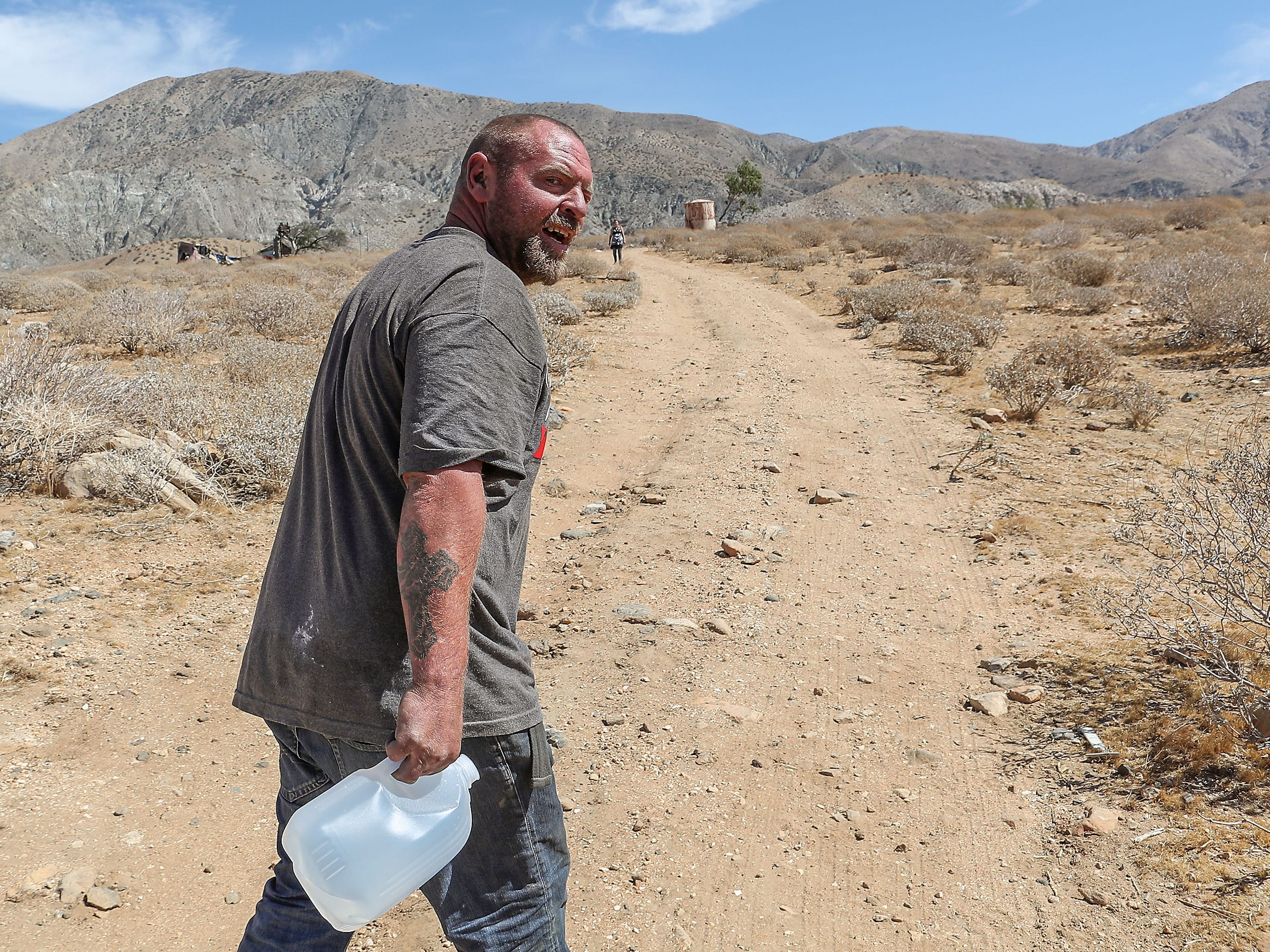 In triple-digit temperatures, Bryan Hensley carries water to a burned down house in Whitewater where he and Carene moved to in  June 2018 after their motel voucher ended.