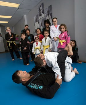 Gracie Jiu-Jitsu instructor, Marcello Alcantar, demonstrates his technique using on a student volunteer during a class at the Pace dojo on Friday, Jan. 11, 2019.