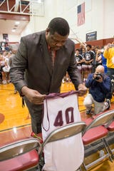 Head coach Clyde Abney places a #40 jersey on a chair during a memorial ceremony in honor of Sean Banks and Antoinette McCoy prior to the Gulf Breeze vs Tate boys basketball at Tate High School in Cantonment on Tuesday, January 15, 2019.  Sean Banks, 15, and sister Antoinette McCoy, 22, were both killed by an alleged drunk driver on Saturday.