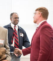 New head football coach Todd Leonard, right, greets fellow PHS alumnus Charles Freeny during a gathering at Pensacola High School in Pensacola on Wednesday, January 16, 2019.