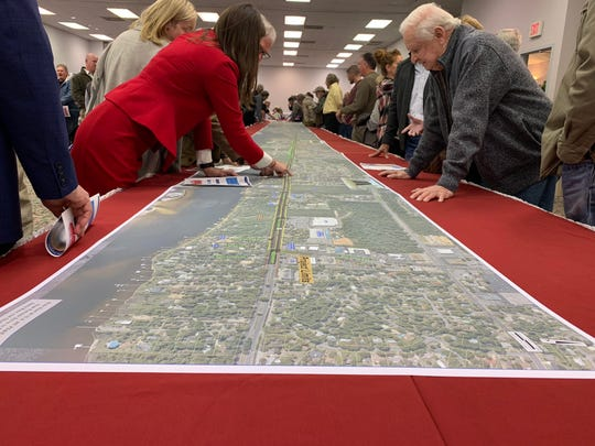 FDOT officials and members of the public go over an overlay photo of what the proposed Highway 98 widening project could look like, and what businesses and neighborhoods might be affected.