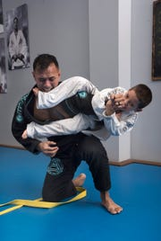 Gracie Jiu-Jitsu instructor, Marcello Alcantar, and demonstrates his technique to a student, Daemeon Coleman, during a class at the Pace dojo on Friday, Jan. 11, 2019.