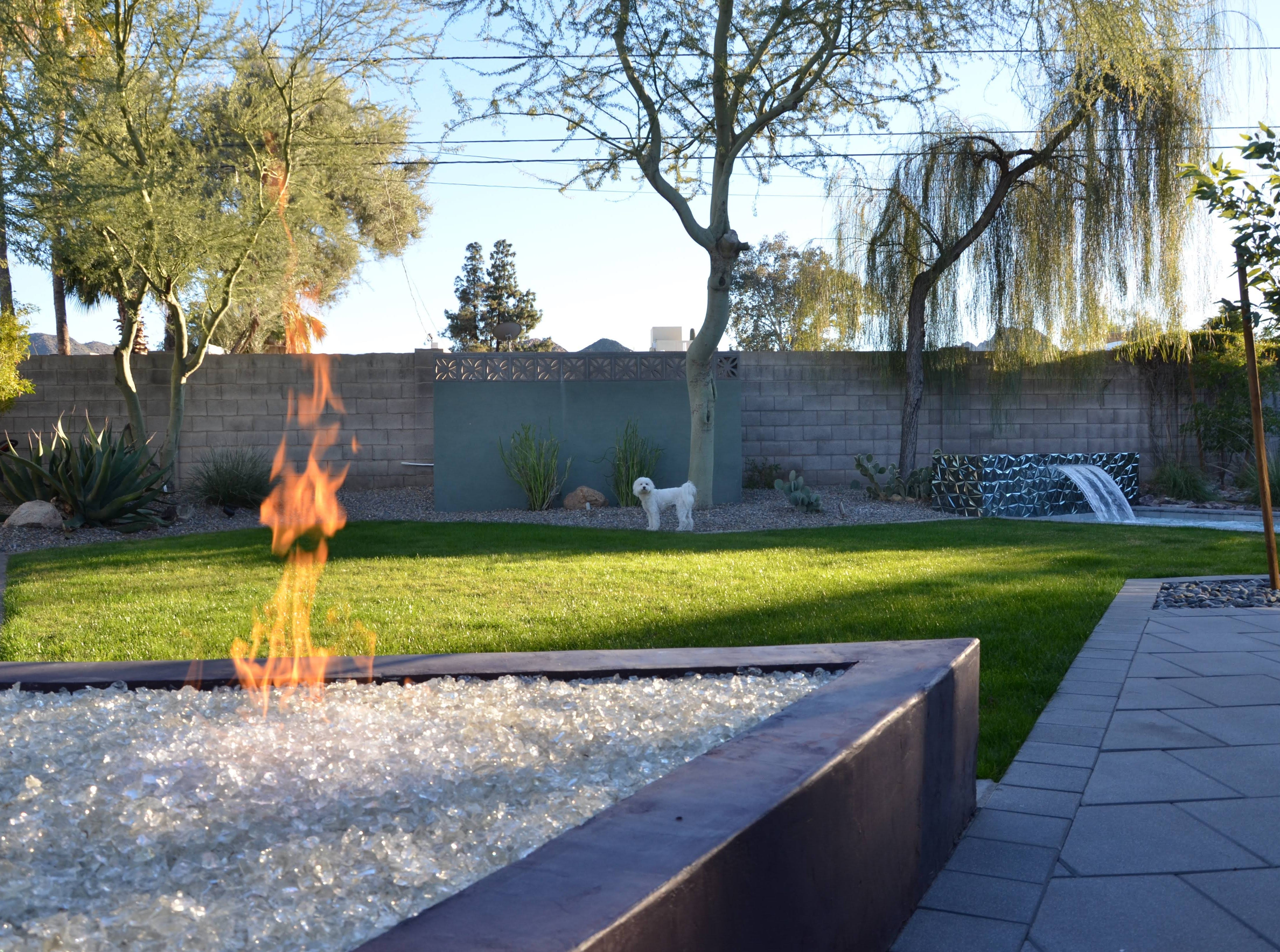 A triangular fire pit sits just off the outdoor dining area, and caught the eye of the Kaye's dog, Rocky.