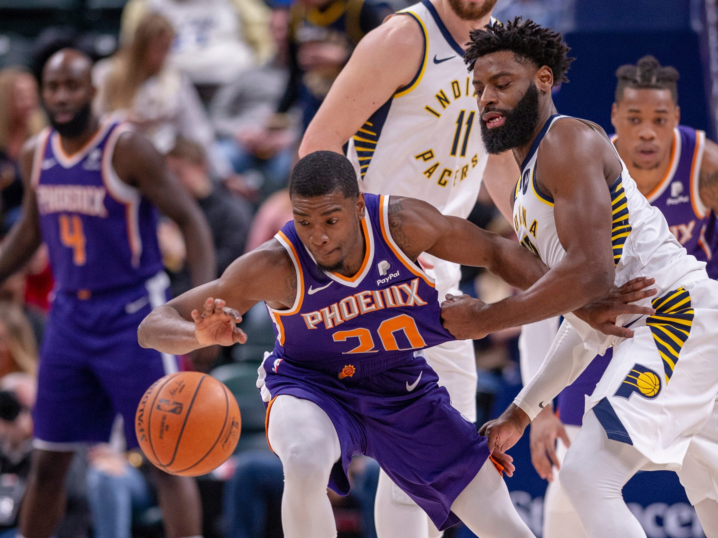 Phoenix Suns forward Josh Jackson (20) is pulled away from the loose ball by Indiana Pacers guard Tyreke Evans (12) during the first half of an NBA basketball game Tuesday, Jan. 15, 2019, in Indianapolis.