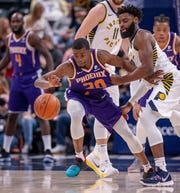 Suns forward Josh Jackson (20) is pulled away from the loose ball by Pacers guard Tyreke Evans on Tuesday.