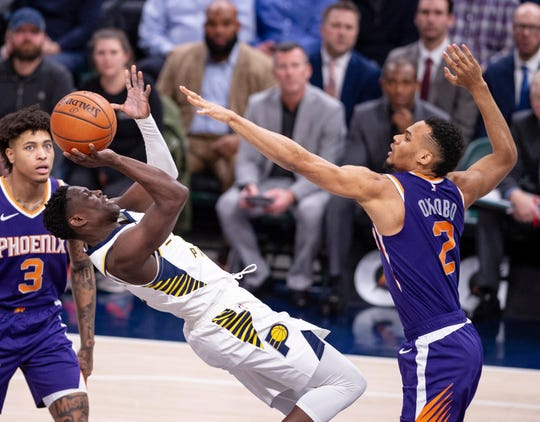 Indiana Pacers guard Victor Oladipo (4) falls backward as he works to get a shot off while being defended by Phoenix Suns guard Elie Okobo (2) during the second half of an NBA basketball game Tuesday, Jan. 15, 2019, in Indianapolis. The Pacers won 131-97.