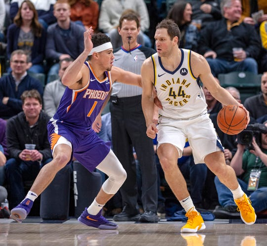 Phoenix Suns guard Devin Booker (1) guards Indiana Pacers forward Bojan Bogdanovic (44) as he works the ball toward the basket during the first half of an NBA basketball game Tuesday, Jan. 15, 2019, in Indianapolis. (AP Photo/Doug McSchooler)