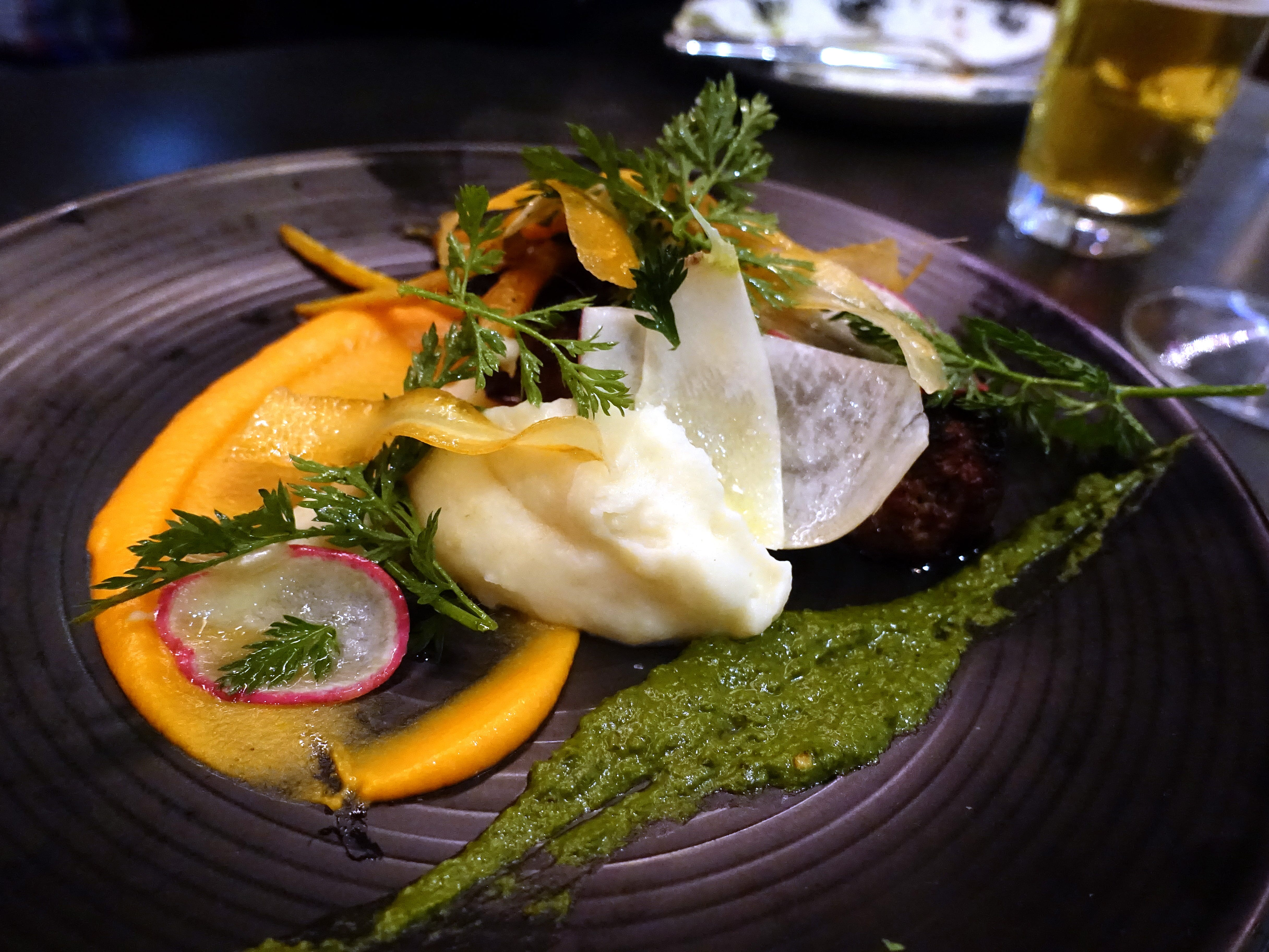 """BBQ'd"" meatloaf with variations of carrot, turnip, potato and carrot top chimichurri at The Larder + The Delta in Phoenix."