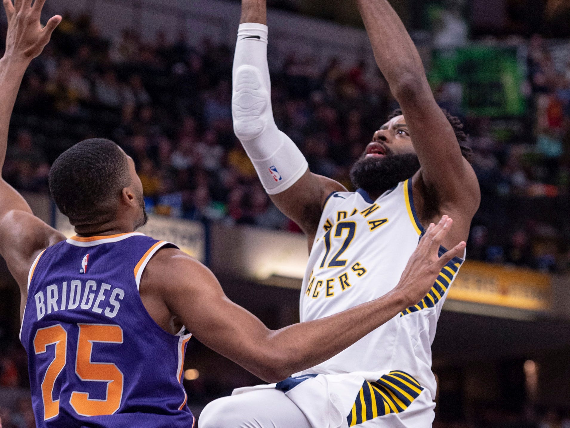 Indiana Pacers guard Tyreke Evans (12) is defended by Phoenix Suns forward Mikal Bridges (25) during the second half of an NBA basketball game Tuesday, Jan. 15, 2019, in Indianapolis. The Pacers won 131-97.