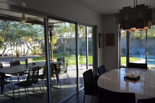 The home's dining area is surround by sliding glass doors, which lead to new dining areas outdoors, thanks to a recent backyard renovation.
