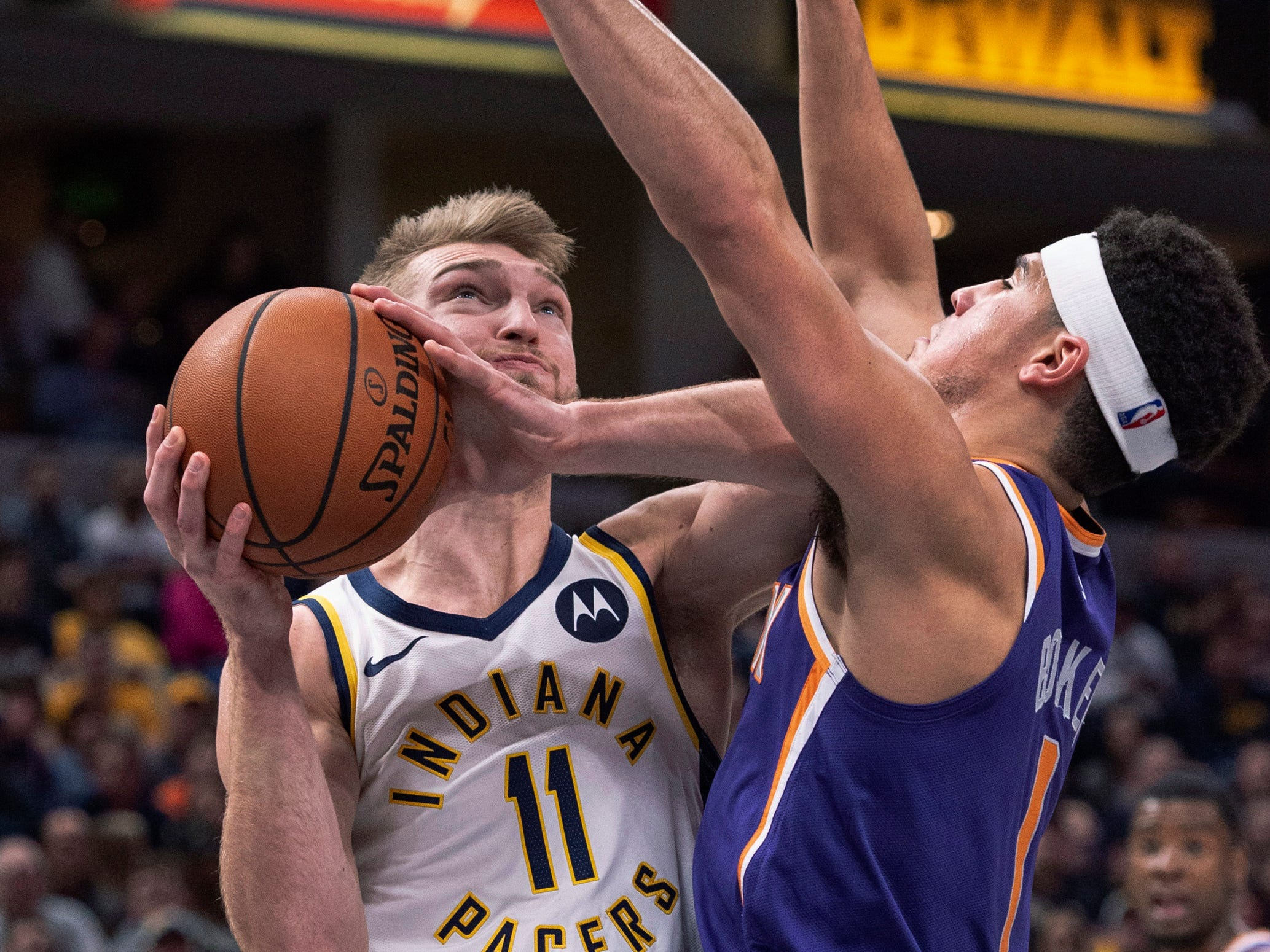 Indiana Pacers forward Domantas Sabonis (11) drives to the basket as Phoenix Suns guard Devin Booker (1) defends during the second half of an NBA basketball game Tuesday, Jan. 15, 2019, in Indianapolis. The Pacers won 131-97.