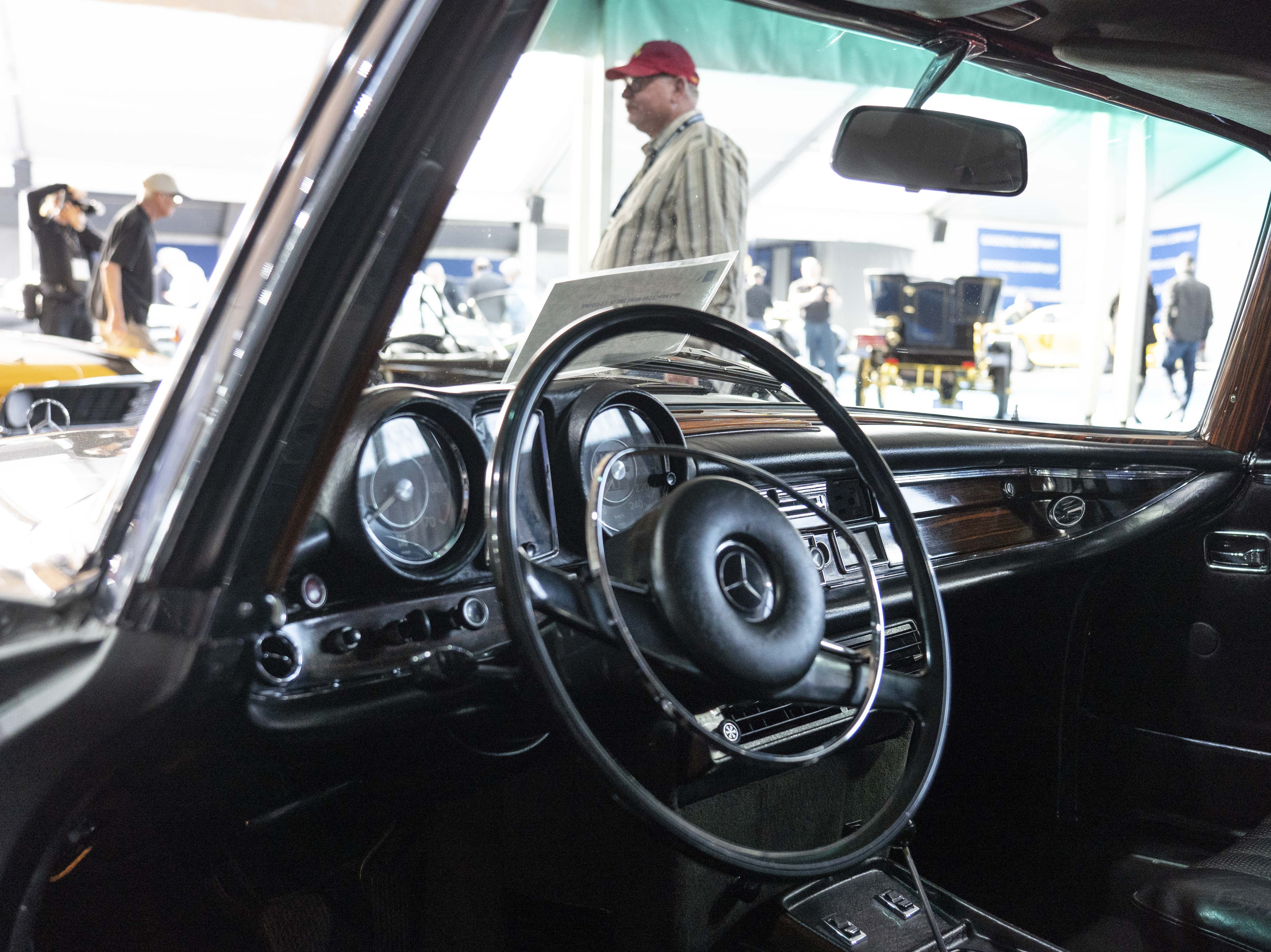 Car fans look at different cars for auction at Gooding & Co.'s preview day in Scottsdale.