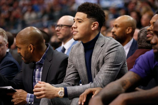 Phoenix Suns guard Devin Booker looks on from the bench during the first half of an NBA basketball game against the Dallas Mavericks, Wednesday, Jan. 9, 2019, in Dallas. Booker did not play due to an earlier injury. (AP Photo/Jim Cowsert)