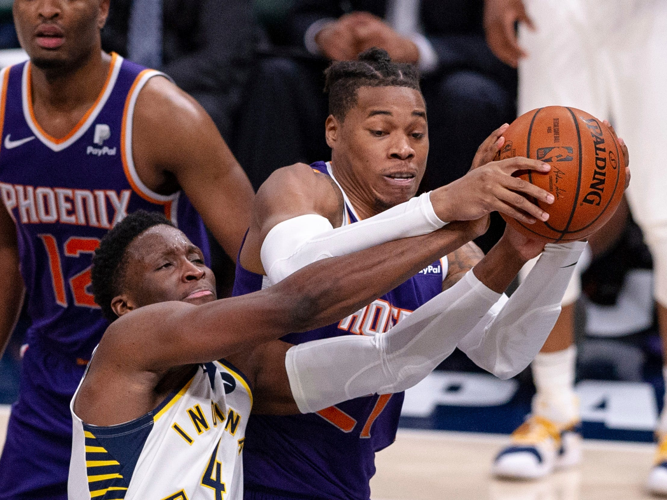 Indiana Pacers guard Victor Oladipo (4) competes for the ball with Phoenix Suns forward Richaun Holmes (21) during the second half of an NBA basketball game Tuesday, Jan. 15, 2019, in Indianapolis. The Pacers won 131-97.