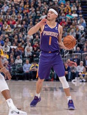 Phoenix Suns guard Devin Booker (1) works the ball around the court during the first half of an NBA basketball game against the Indiana Pacers Tuesday, Jan. 15, 2019, in Indianapolis. (AP Photo/Doug McSchooler)