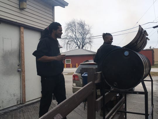 From left, Jamacian Jerk owner Mark Pack and cook Adrien Lee prepare rip tips and jerk chicken on a bbq smoker on Jan. 15, 2019.