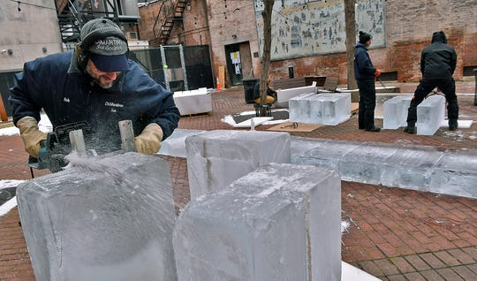 Rob Higareda of  DiMartino Ice Company uses an electric chainsaw to cut a block of ice while building a 40-foot ice slice for the annual FestivICE event on Cherry Lane, Wednesday, January 16, 2019.