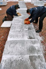 Rob Higareda, left, and Dave DeFloria of DiMartino Ice Company smooth 265 pound blocks of ice creating the base of  a 40-foot ice slice for the annual FestivICE event on Cherry Lane, Wednesday, January 16, 2019.