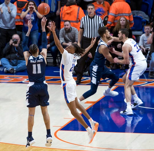 Nevada forward Cody Martin pulls up to hit the winning three-point shot while defended by Boise State's Derrick Alston on Tuesday.