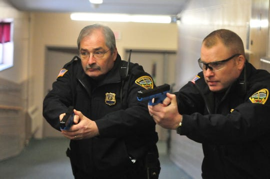 Chief Jim Branum and Major Jon Bales carefully approach a corner during an active-shooter training scenario Wednesday at the former Pleasant View school building.