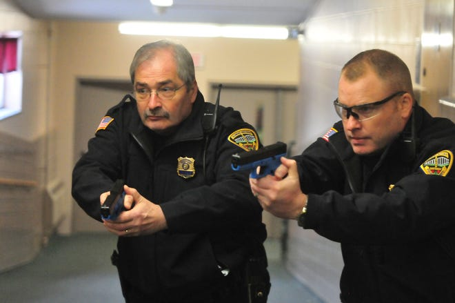 Chief Jim Branum and Major Jon Bales carefully approach a corner during an active-shooter training scenario at the former Pleasant View school building.