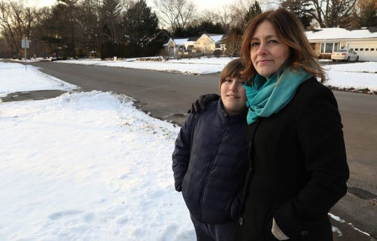 Julian Moore, 10, and his mother, Jenny Moore, stand near the spot where Julian was hit on his bike on Kilbourn Road in Pittsford, down the road from Oak Hill Country Club.