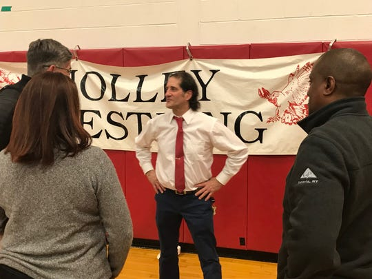 John Grillo talks with well-wishers after the Holley-Kendall team won its final home match of this season, his final one as a high school coach.