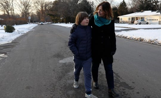 Julian Moore and his mother, Jenny Moore, walk near the spot on Kilbourn Road where Julian was hit while bicycling.
