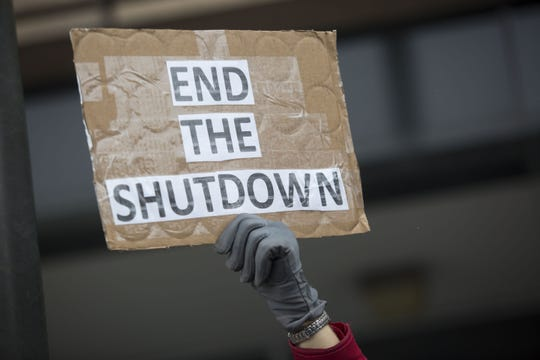 A demonstrator holds a sign protesting the government shutdown at the James V. Hansen Federal Building on January 10, 2019 in Ogden, Utah. As the shutdown nears the three week mark, many federal employees will not receive a paycheck tomorrow.