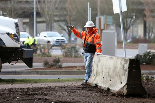 City workers place concrete barriers under the Marion Street Bridge in Salem on Wednesday, Jan. 16 2019. (MICHAELA ROMÁN / Statesman Journal)
