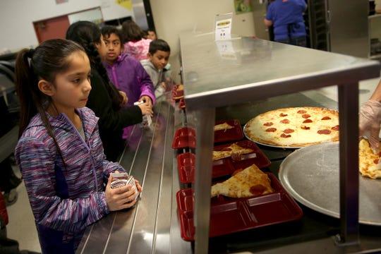 Fourth grade student Scarlett Ruiz waits for pizza at Auburn Elementary School in Salem on Wednesday, Jan. 16 2019.