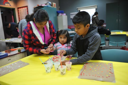 A family works on drip-style paintings at the Alisal Family Resource Center on Tuesday.
