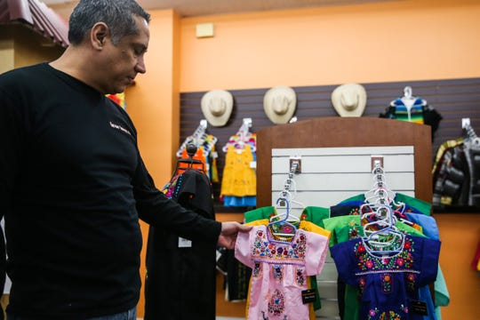 Hector Leos touches a traditional Mexican dress on display Wednesday, Jan. 16, 2019, at Leos Imports.