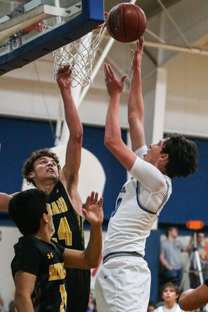 Eden's Hunner Rodgers, right, goes up for a shot against Menard's Kallin Kothmann during a District 12-1A boys basketball game in 2019.