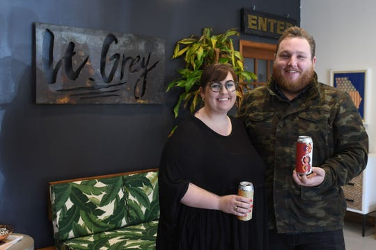 Taylor Harman and Harrison Albert, Co-Owners of Lt Grey Creative in West Ocean City, hold some samples of their work with Dewey Beer Co.