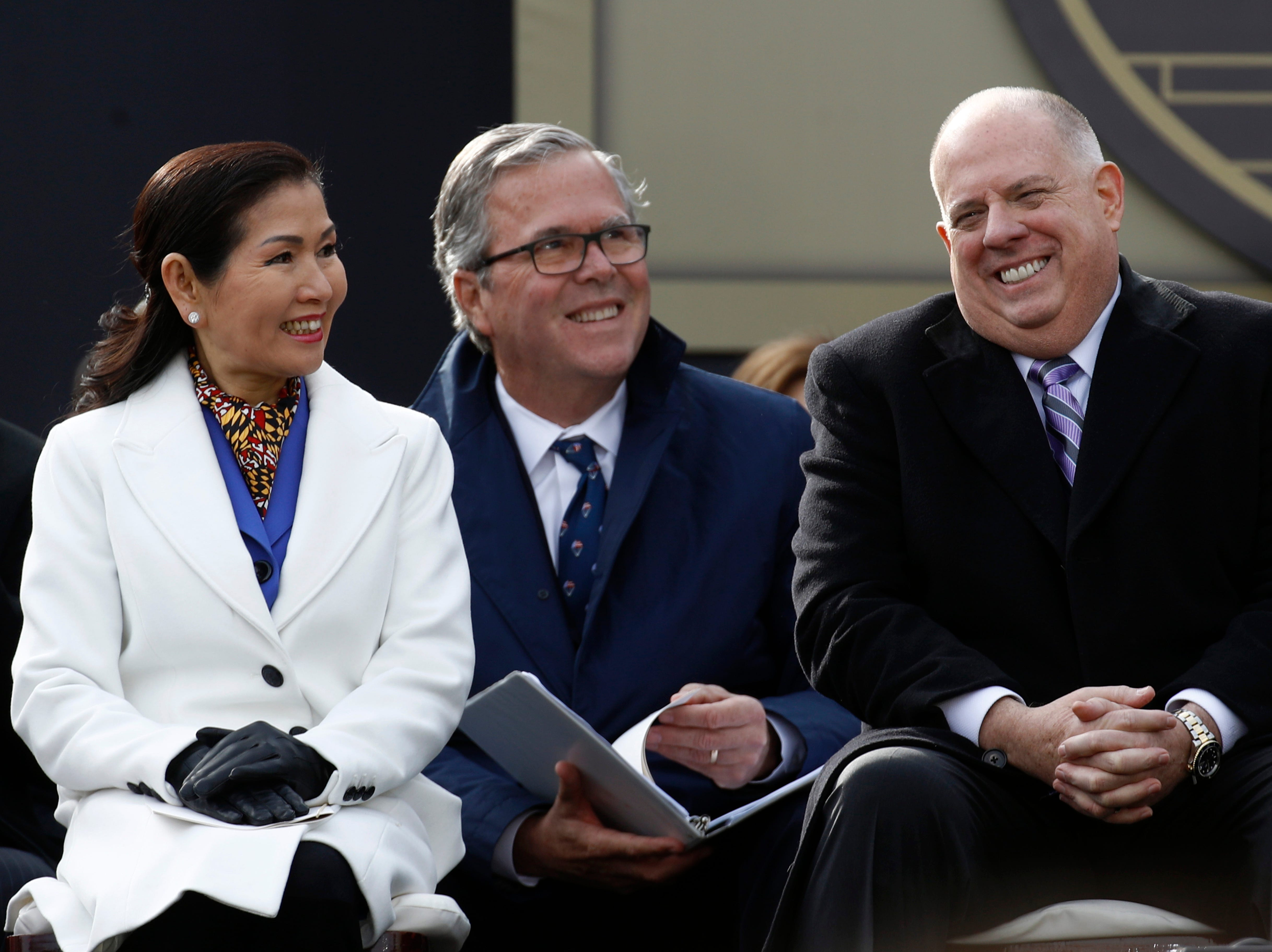 Maryland Gov. Larry Hogan, right, laughs alongside first lady Yumi Hogan, left, and former Florida Gov. Jeb Bush during Hogan's inauguration ceremony Wednesday, Jan. 16, 2019, in Annapolis.