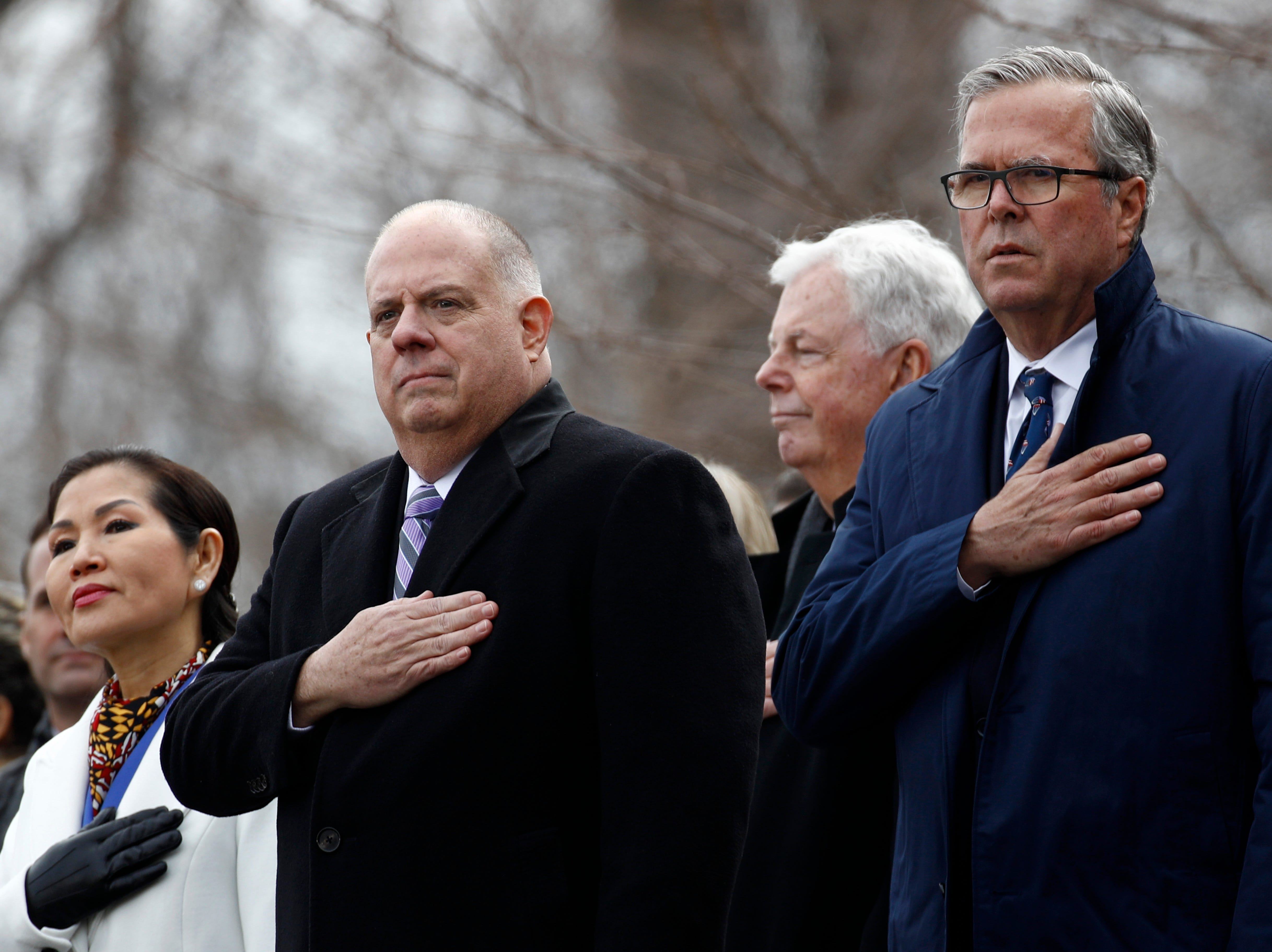 Maryland Gov. Larry Hogan, center, stands between first lady Yumi Hogan, left, and former Florida Gov. Jeb Bush during a rendition of the national anthem at Hogan's inauguration ceremony Wednesday, Jan. 16, 2019, in Annapolis.