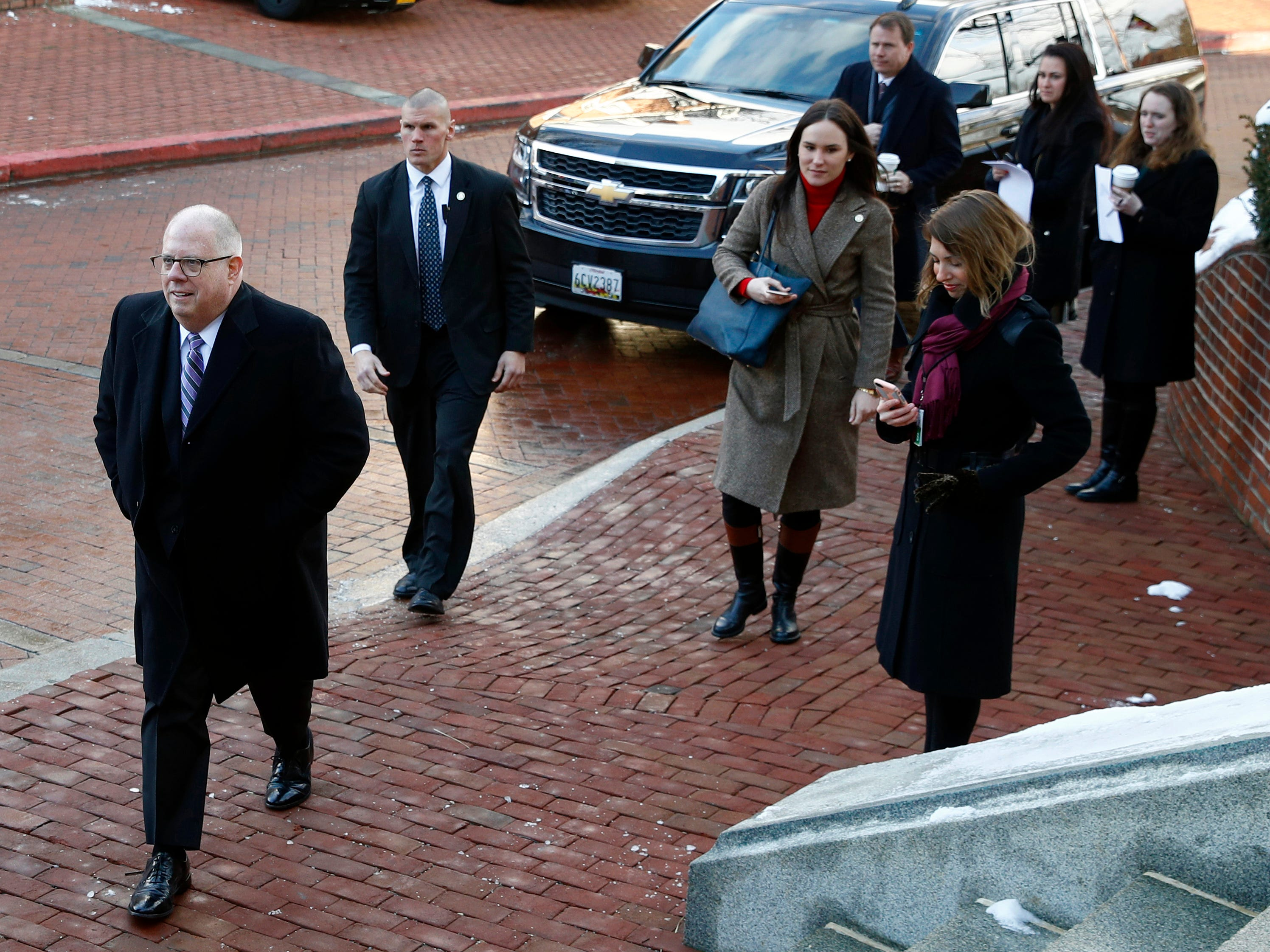 Maryland Gov. Larry Hogan, left, arrives to speak with members of the news media outside the Maryland State House before his inauguration ceremony Wednesday, Jan. 16, 2019, in Annapolis.