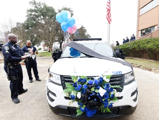 Cpl. Marcus Hines (left) and Cpl. Anthony Kelly lay flowers on the memorialized police car for Police Officer Chateri Payne Wednesday, January 16, 2019, outside the Shreveport Police Station.
