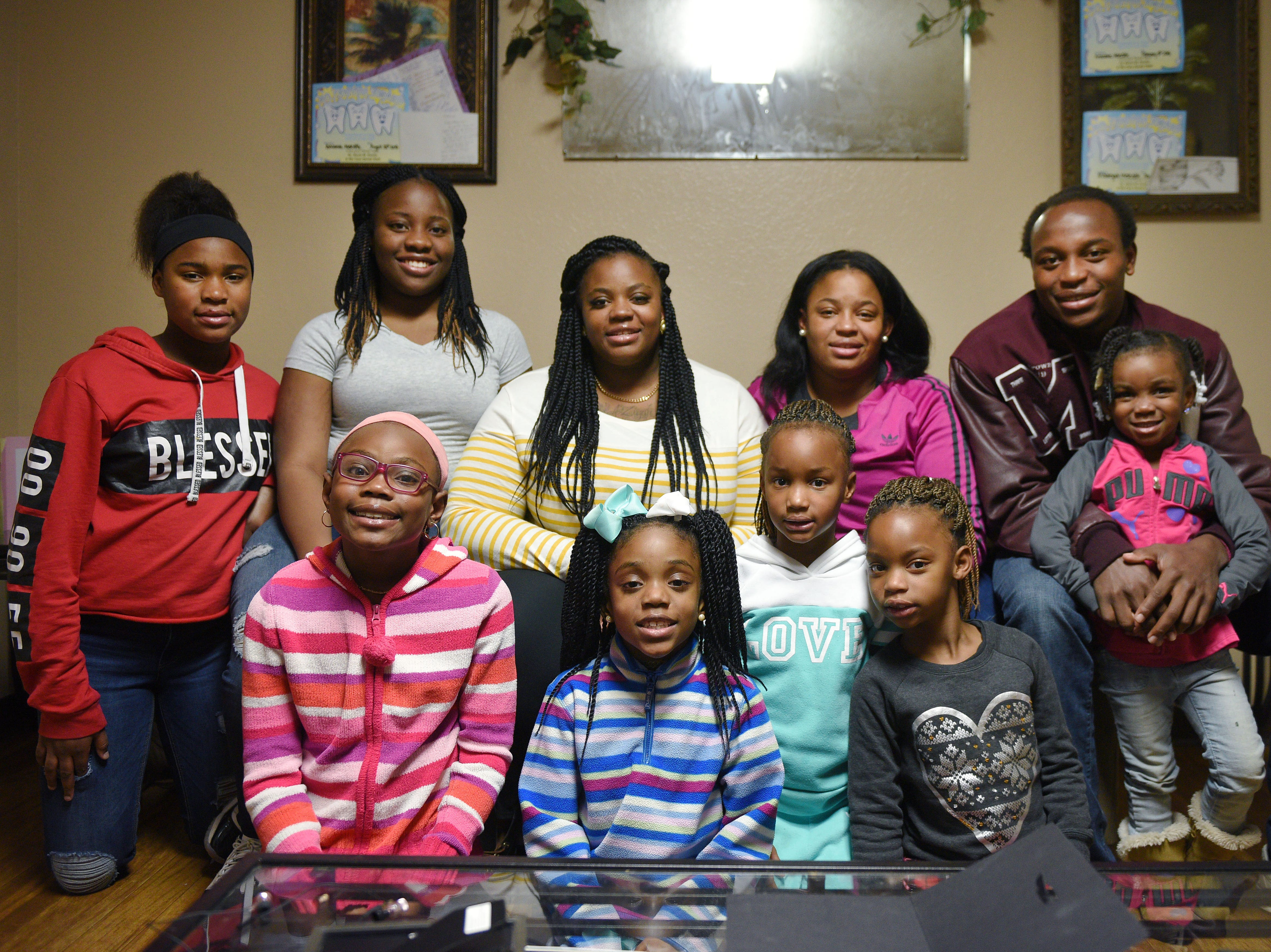 A'Meria Meredith, top row from left, Ka'Sandra Cauley, TanChicca Meredith, Iesha Meredith, Doyle Brown, Ava Scott Brown, bottom row from right, A'Zaireyah Meredith, ARianna Meredith, Aubrey Meredith, and A'Ziyah Meredith pose for a photo with Doyle Brown Thursday, Jan. 9, in Madison.