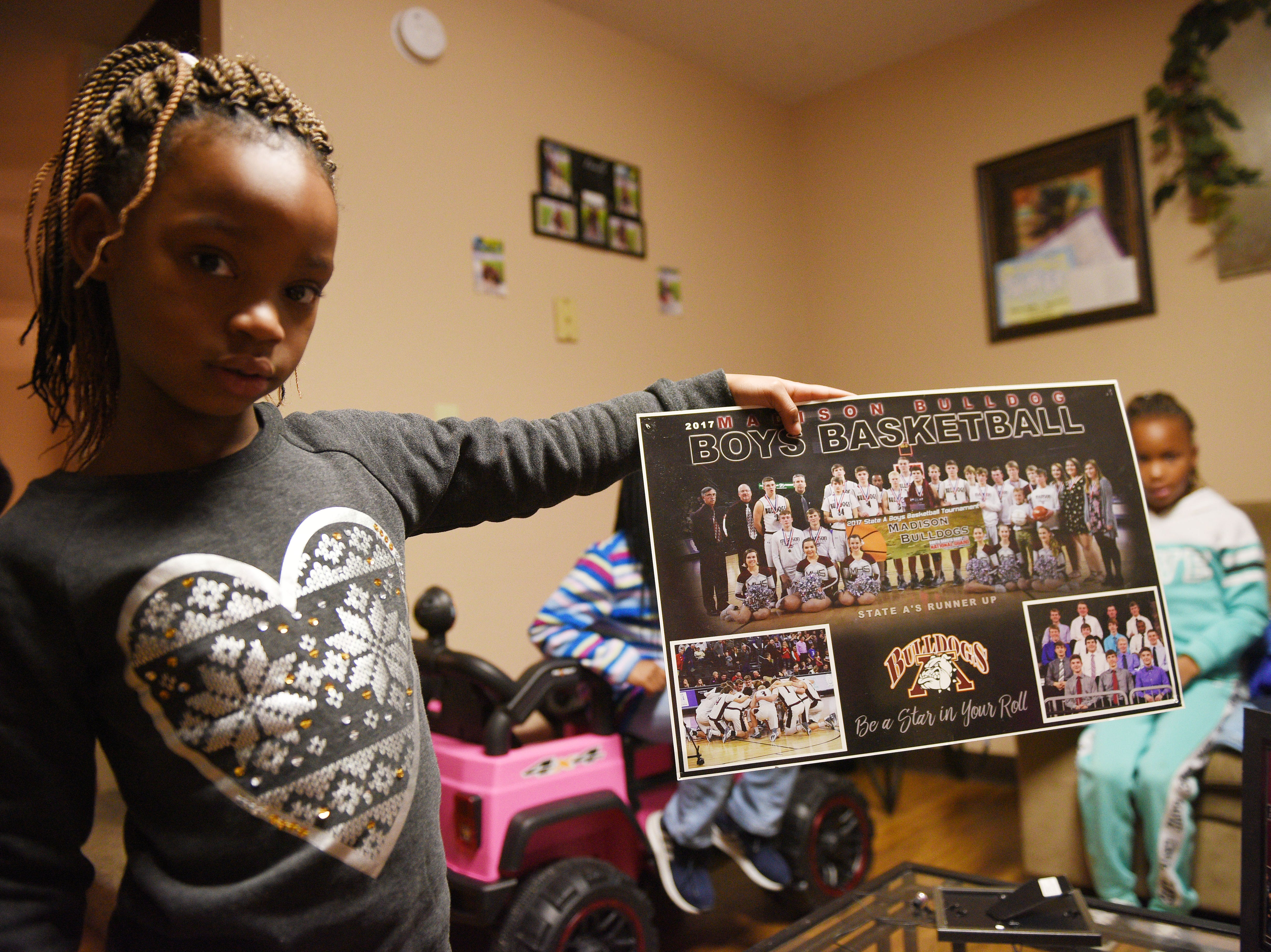 A'Zaireyah Meredith holds up a team photo of Doyle Brown Thursday, Jan. 9, at Iesha Meredith's home in Madison. Doyle's three sisters and six nieces live in Madison.