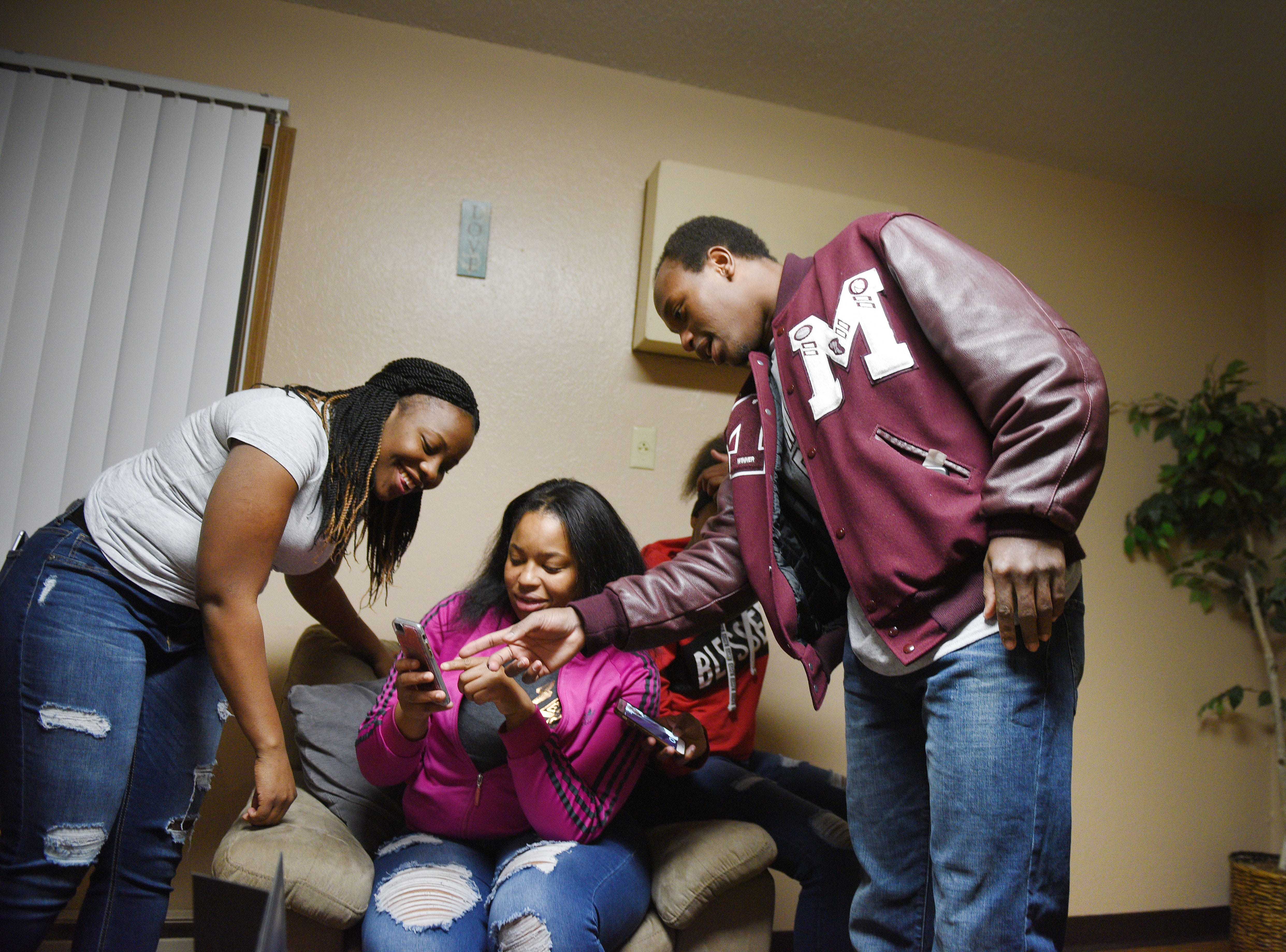 Ka'Sandra Cauley, from left, Iesha Meredith, A'Meria Meredith and Doyle Brown look at old photos of Doyle at Iesha's home Thursday, Jan. 9, in Madison. Doyle Brown moved to Madison from Louisiana with his sister Iesha in 2015.
