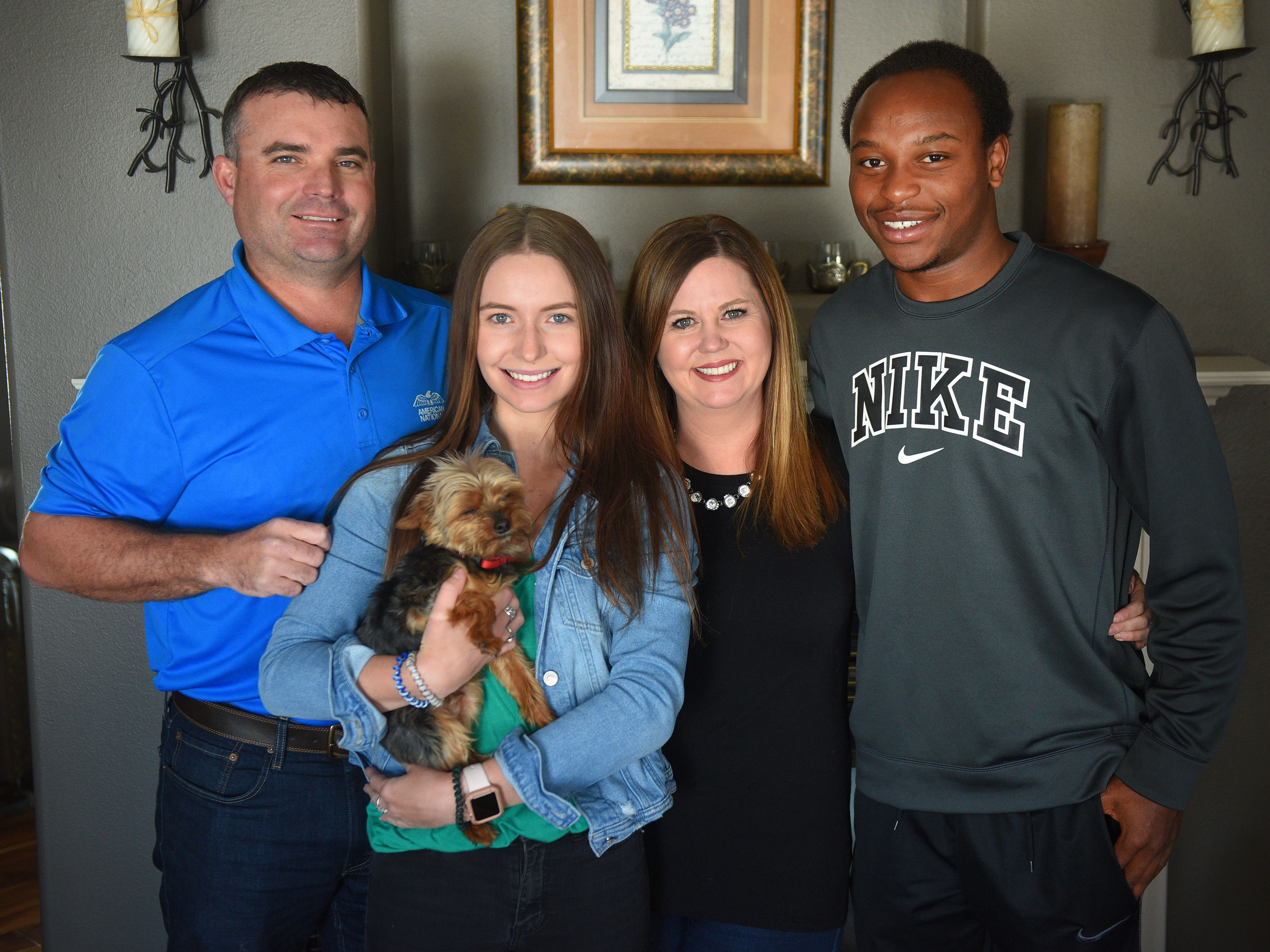 Mike Dorris, from left, Karsyn Dorris, Shanley Dorris and Doyle Brown and their dog Tebow gather for a photo Wednesday, Jan. 16., at Shanley and Mike Dorris' home in Madison. Mike and Shanley started taking care of Doyle after their daughter Karsyn became friends with him at school. Doyle's sisters Lisha and TanChicca live in Madison but they have seven other girls they take care of. Doyle wanted more male role models in his life.