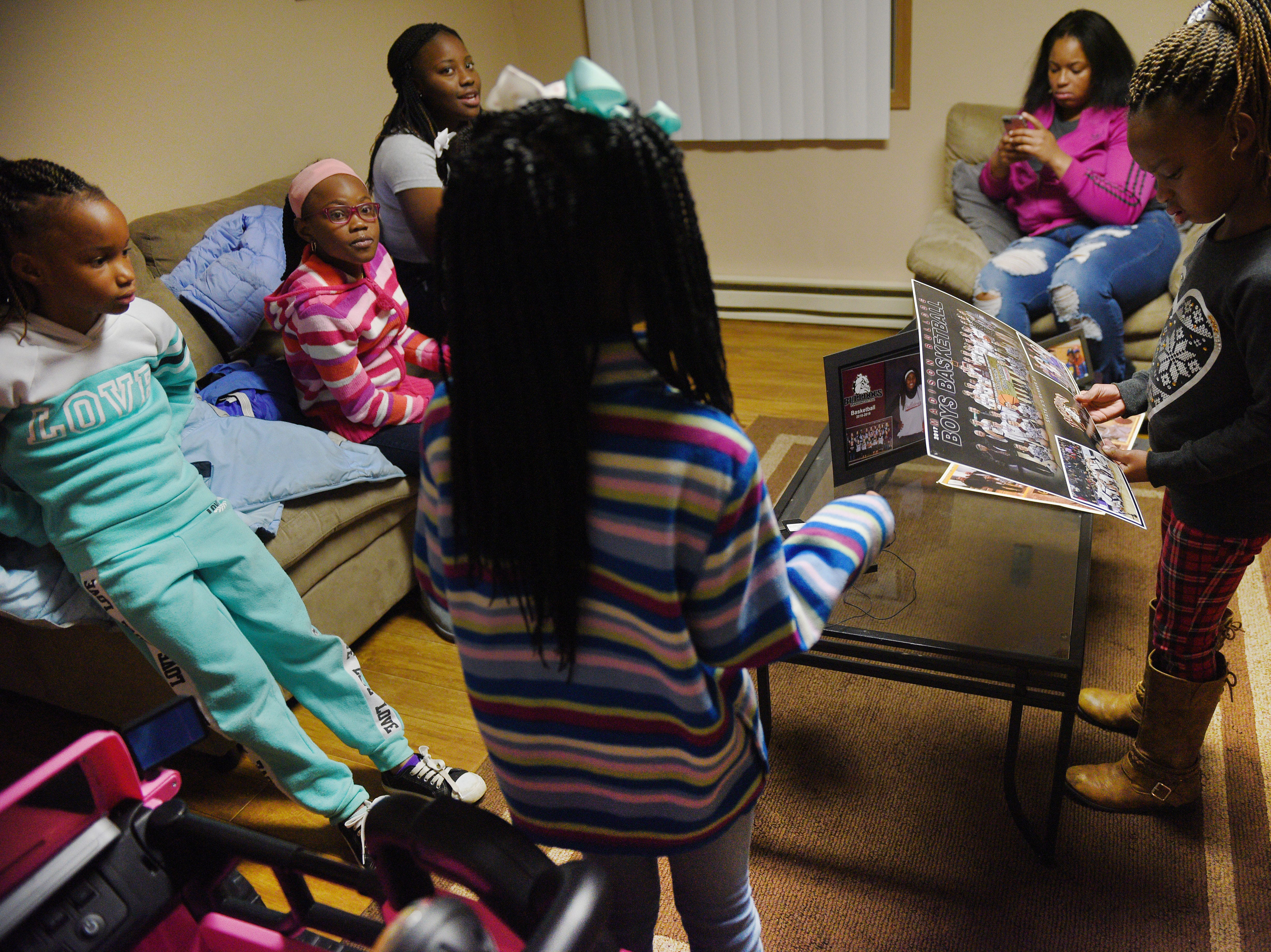 A'Zaireyah Meredith, far right, holds a team photo of Doyle Brown Thursday, Jan. 9, at Iesha Meredith's home in Madison. Doyle's three sisters and six nieces live in Madison.