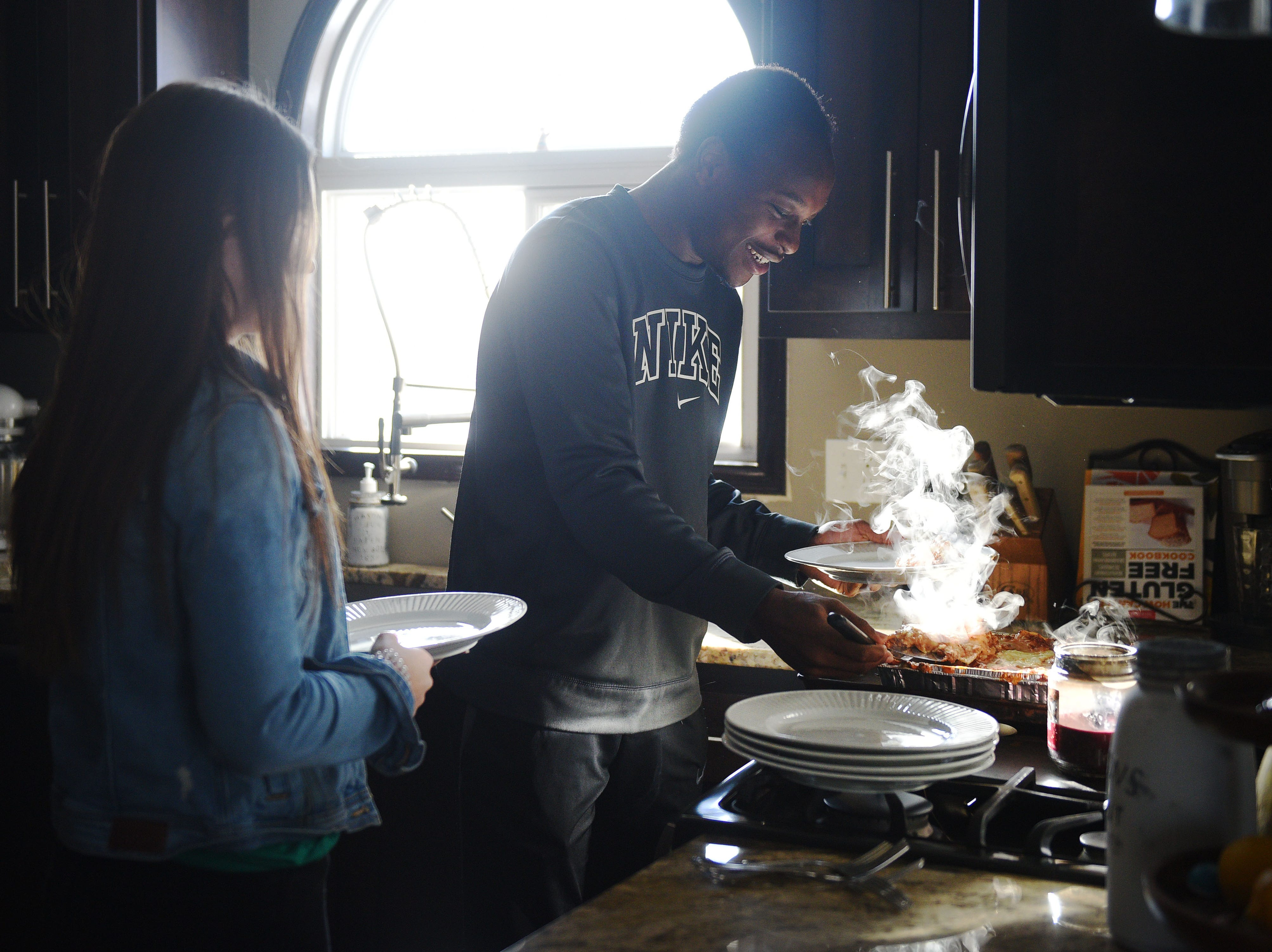Doyle Brown serves himself lasagna with Karsyn Dorris Wednesday, Jan. 16., at their home in Madison. Karsyn refers to Doyle as her brother.