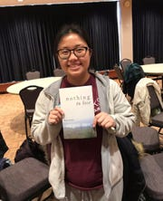 "Pakou Xiong holds a copy of ""Nothing to Lose"" by Kim Suhr."