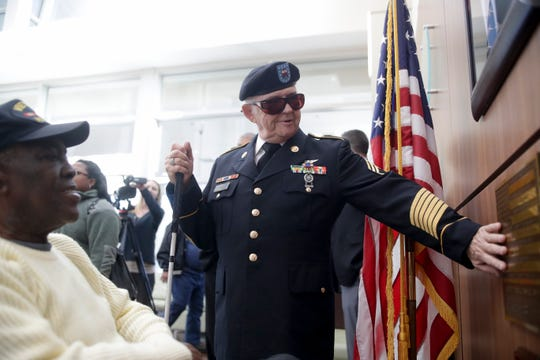 "Walt Peters, who donated the bronze American flag with the Pledge of Allegiance on it in Braille, touches it while chatting with Calvin Ellis, a visually impaired navy veteran from Marianna, after the flag was dedicated during a ceremony at Sergeant Ernest I. ""Boots"" Thomas Veterans Affairs Clinic in Tallahassee Wednesday, Jan. 16, 2019."